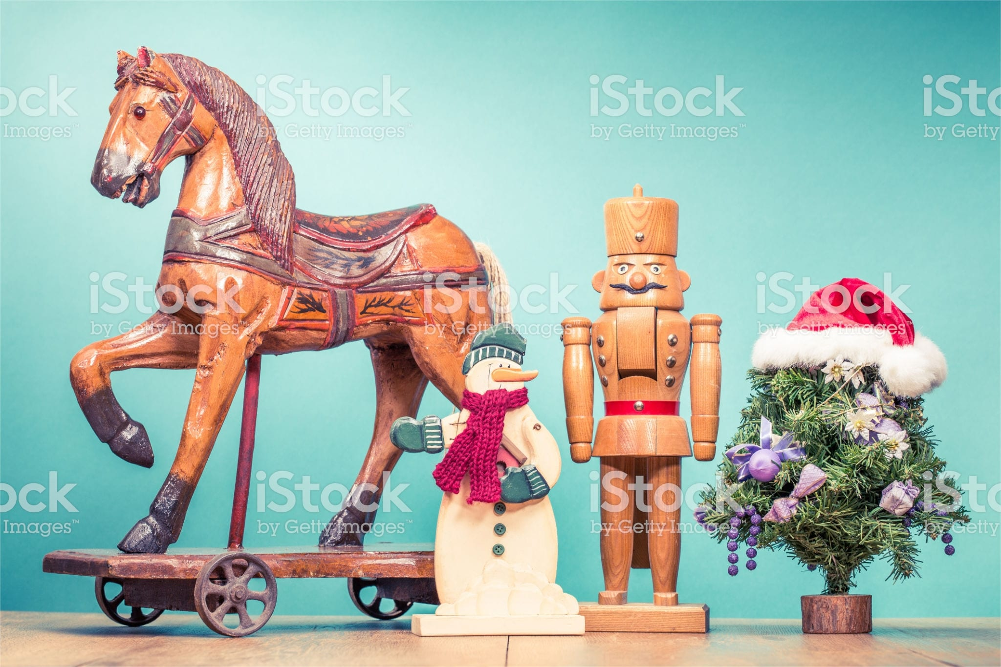 Retro antique Christmas wooden horse on wheels toy, old snowman, nutcracker and New Year tree in Santa's hat. Holiday greeting card. Vintage style filtered photo