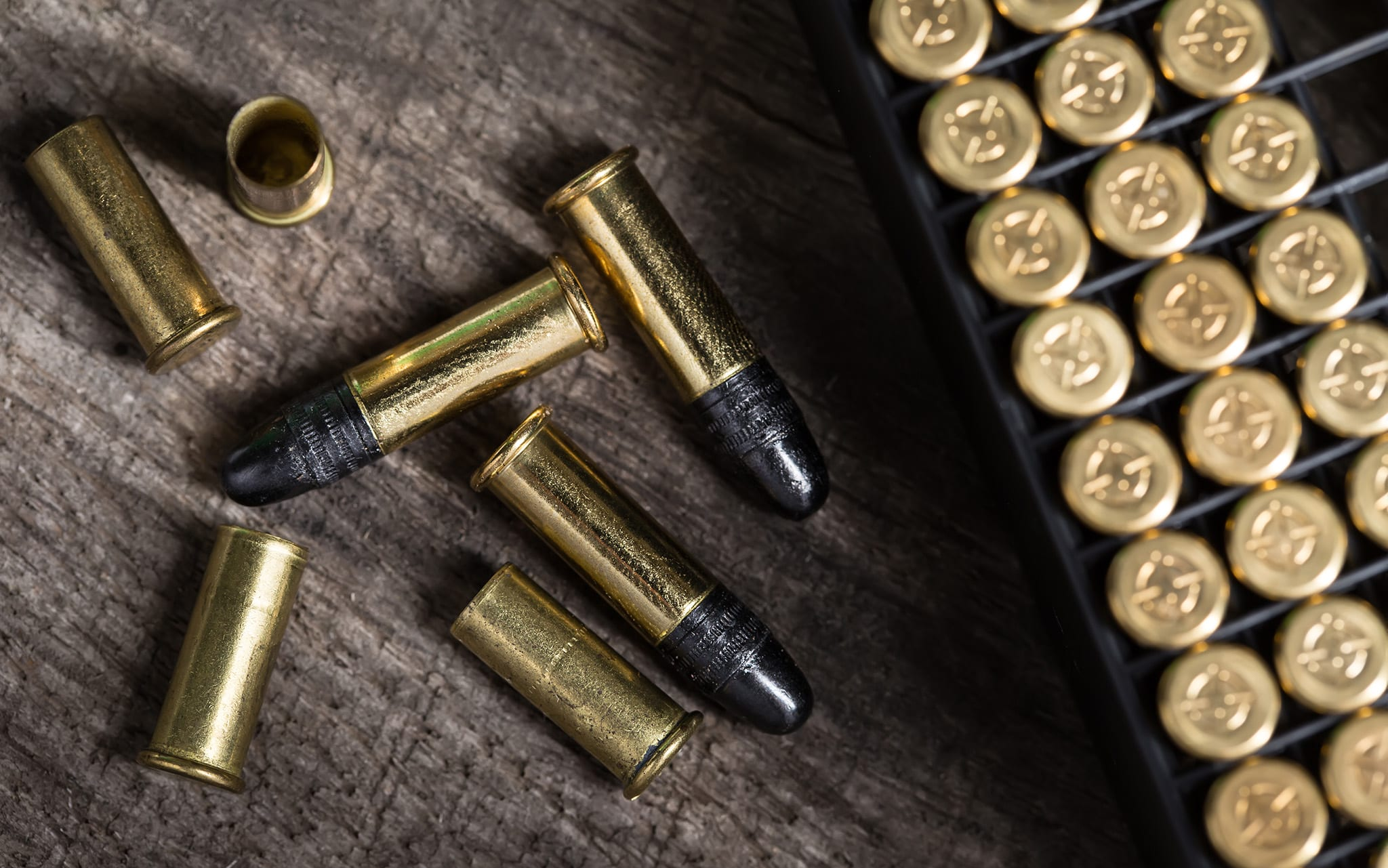 Scattering of small caliber cartridges on a wooden background. Other cartridges cartridges lies in capsules up. The picture from the top point.