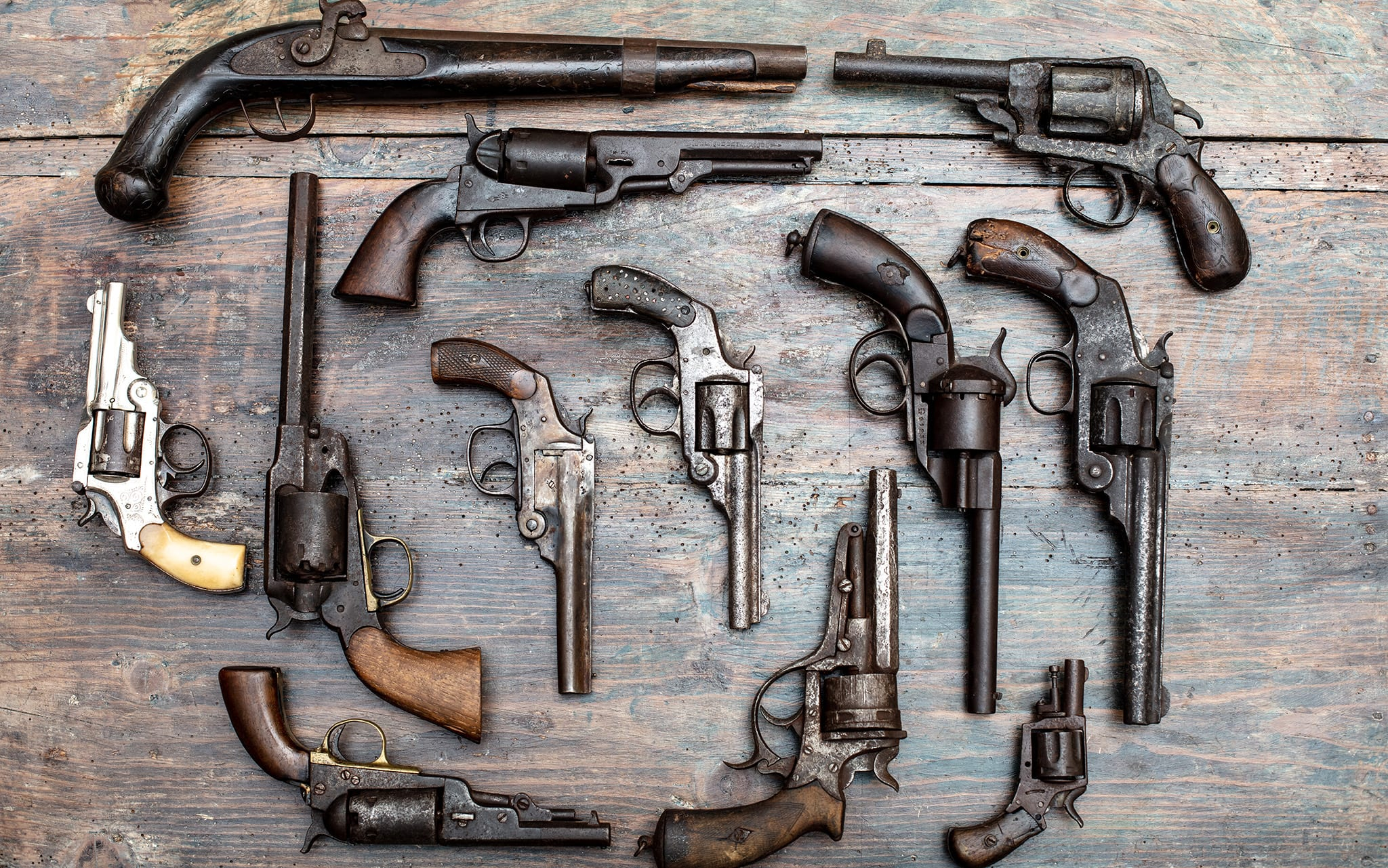 Armory display of historic guns and pistols in a overhead view on a vintage wooden table background